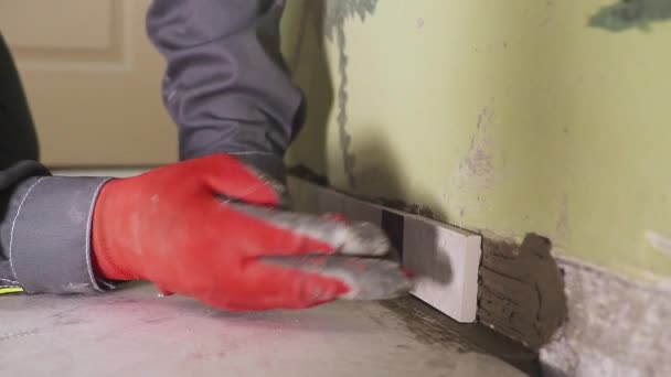 Lavoratore imposta piccole piastrelle sul muro in cucina le mani