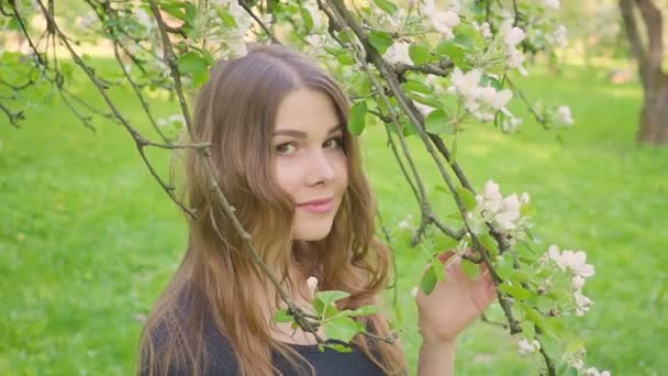 young happy woman walking in an apple orchard in the spring flowers white. Portrait of a beautiful girl