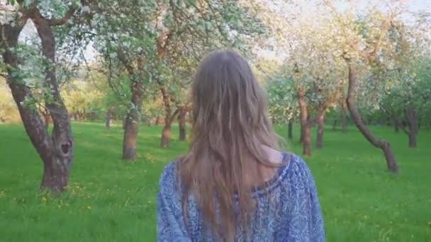 lákavé mladá žena v jabloňový sad v bílé jarní květiny. Portrét krásné dívky v zahradě ovoce večer.