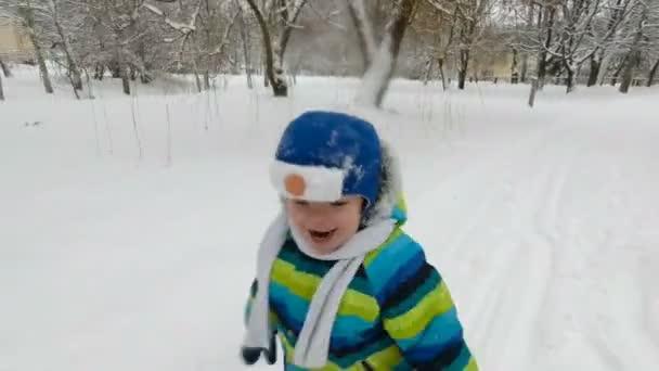 glücklicher kleiner Junge läuft im Winter im Park. fröhlicher Junge, der Spaß in einem Schnee-Winterpark hat. Lächelnd. Weicher Fokus