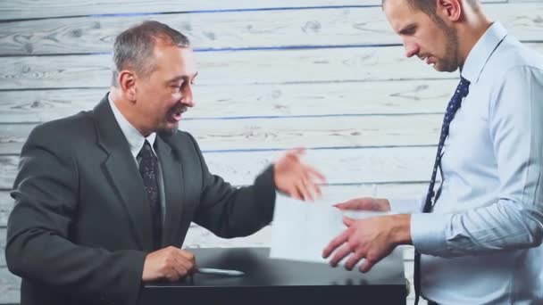 Two businessmen in negotiations discuss a contract.