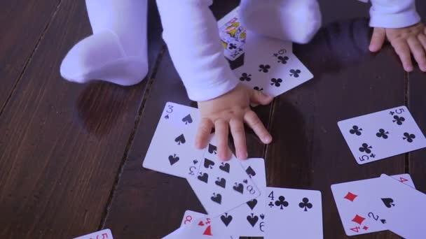 Novorozené dítě hraje hrací karty v místnosti