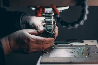 Hands of worker changing cutter in CNC milling machine