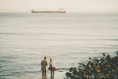 Two people on winter beach and cargo ship in distance