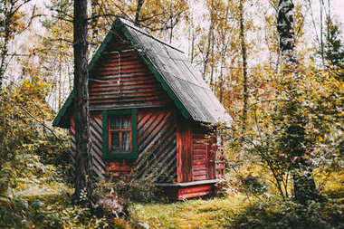 Wooden house in fall forest
