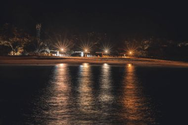 Night beach with light reflections on the water