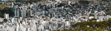 Panoramic shot of an urban landscape from high above of Juiz de Fora town in Minas Gerais state of Brazil: multiple multistorey residential and office buildings, favelas, parks, and hills, bright day stock vector
