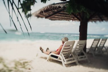 Caucasian senior tourist on the resort daybed next to sea