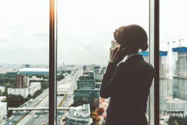 African female phoning near a window