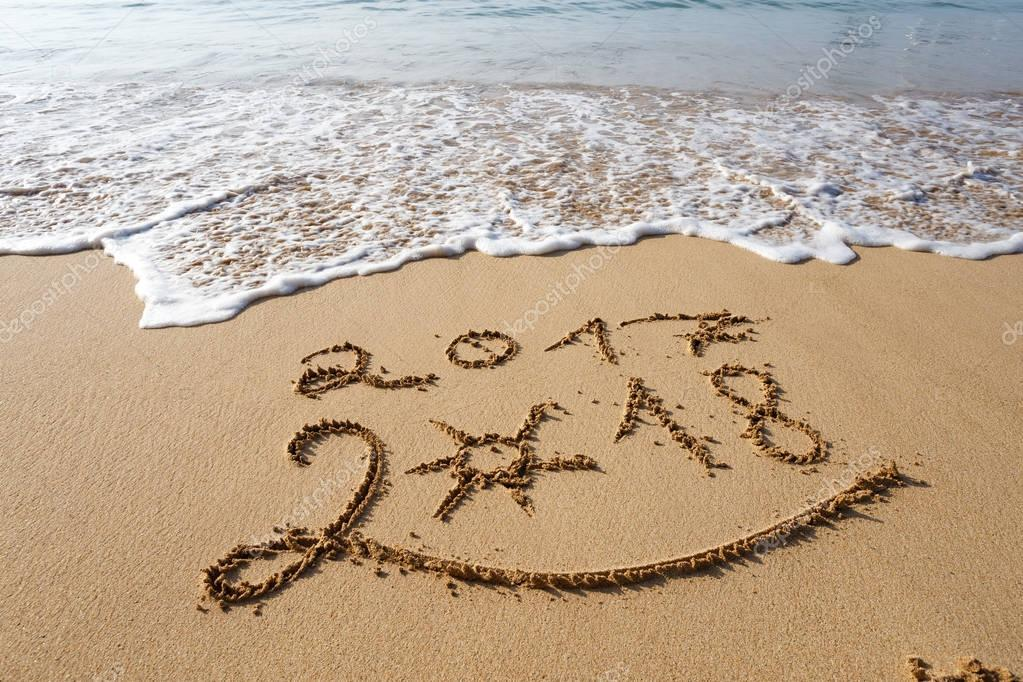 Happy New Year 2018 lettering on tropical beach sand