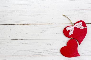 A red wooden heart on a white wooden background. Valentine's day