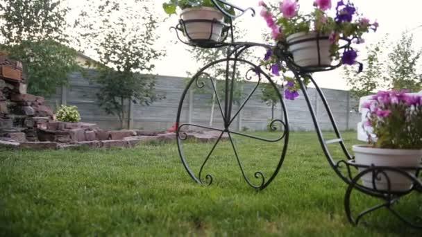 unter einem Blumentopf in Form eines Fahrrads stehen