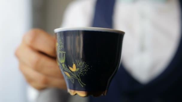 Equipaggia le mani che tiene tazza di caffè