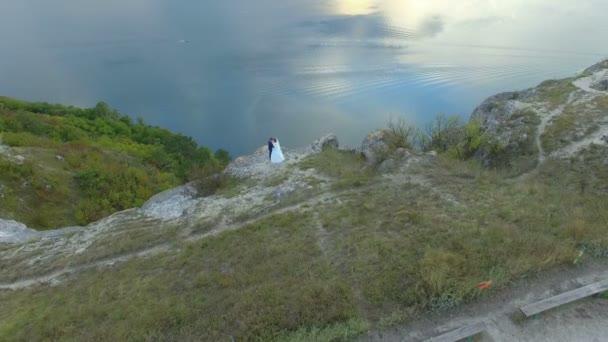 Skvělá západ slunce na jezeře mezi horami. Pár objímání na okraji útesu. 4k