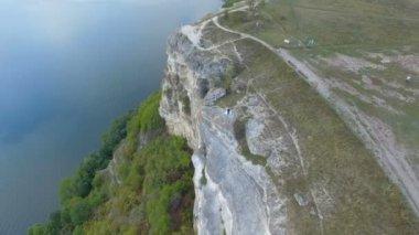 Nagy naplemente a tó, a hegyek között. Egy pár átölelve a szikla szélén. 4k. Légi