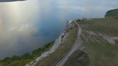 Nagy naplemente a tó, a hegyek között. Egy pár átölelve a szikla szélén. 4k