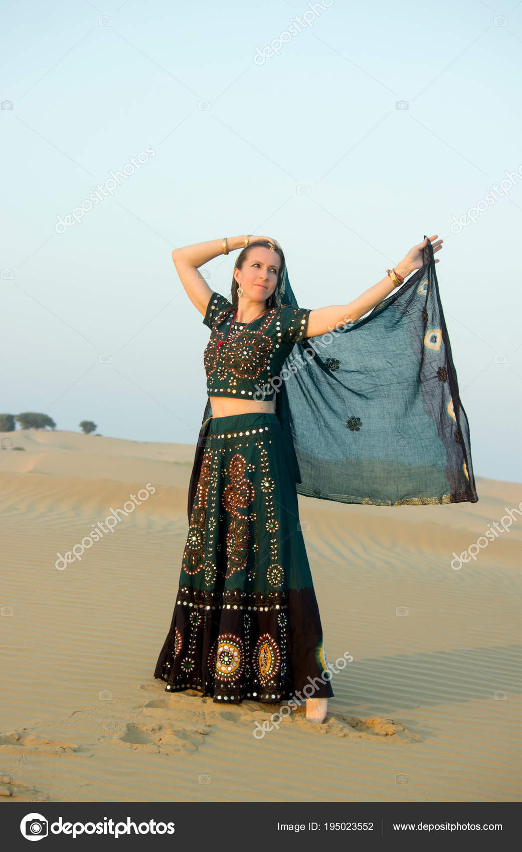 e781efc66d A young woman in Indian national clothes, lit by the setting sun, dancing  in the sands of the Thar Desert, waving a veil. Rajasthan, India.– stock  image