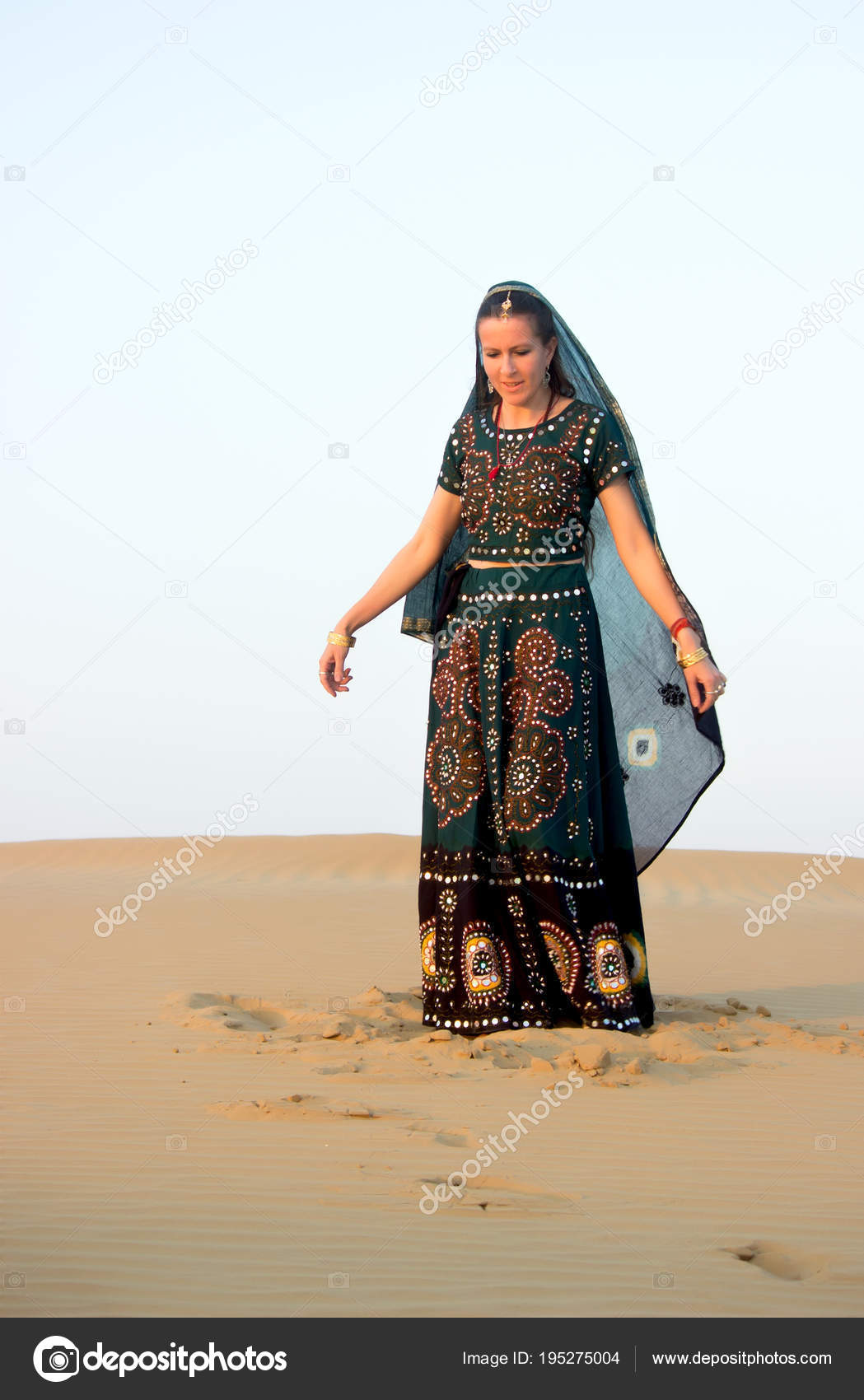 5d23ec1025 A young woman in Indian national clothes looks thoughtfully at the sand,  standing under the setting sun in dunes of the Tar desert. Rajasthan, India.