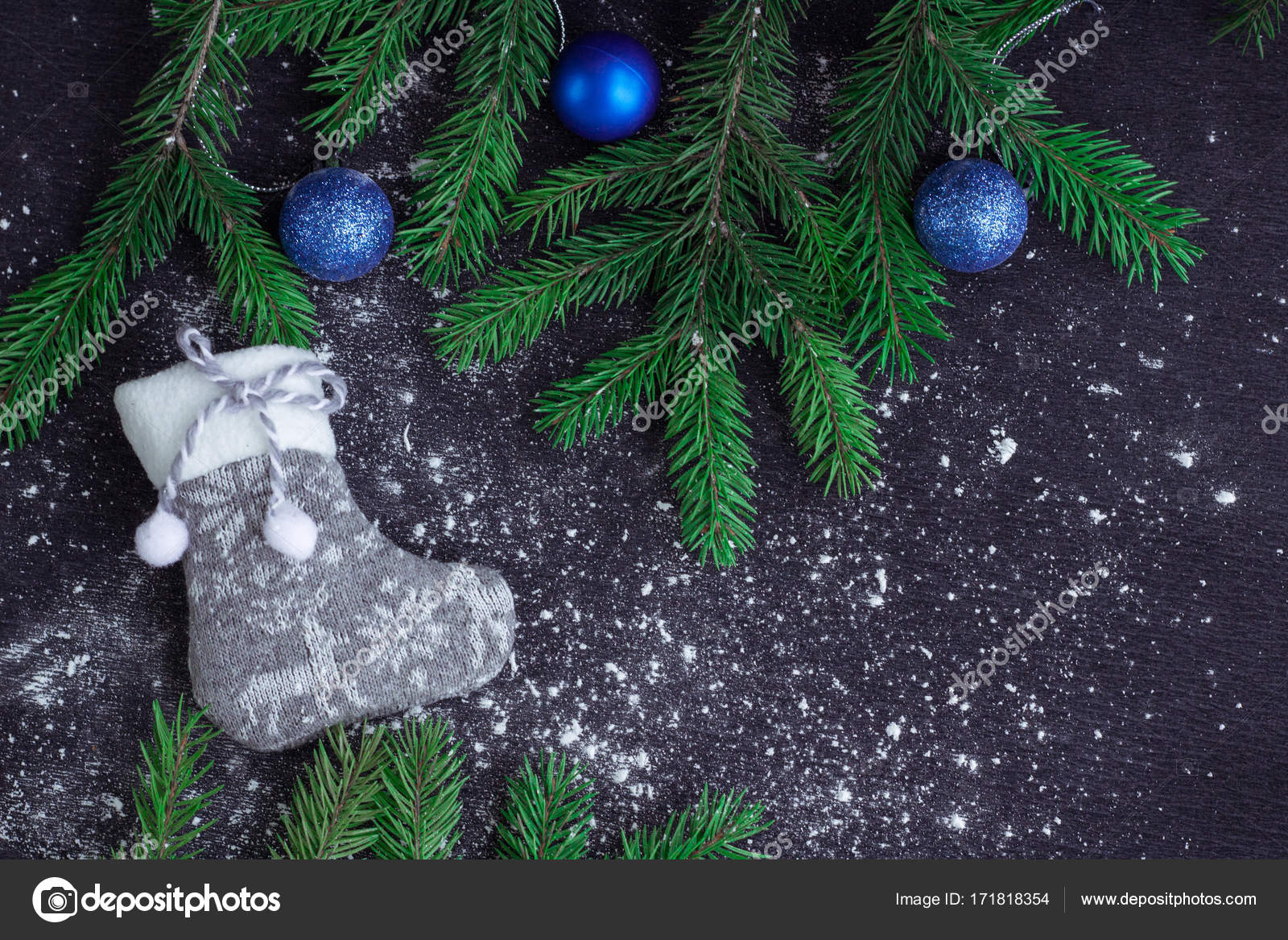 christmas and new year winter holiday snowbound composition of grey stocking on black space background with green fir tree branches and blue balls ornament - Blue Grey Christmas Decorations