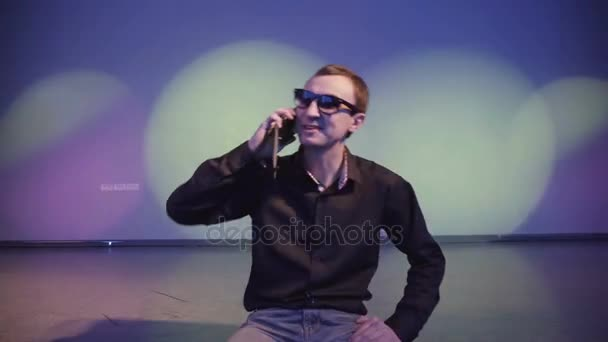 Confident man in a nightclub talking on cell phone