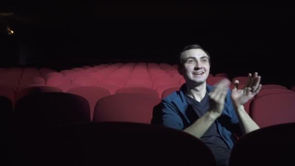 Az ember ül a kényelmes piros székek, a sötét mozi Színház vallomásáért, és