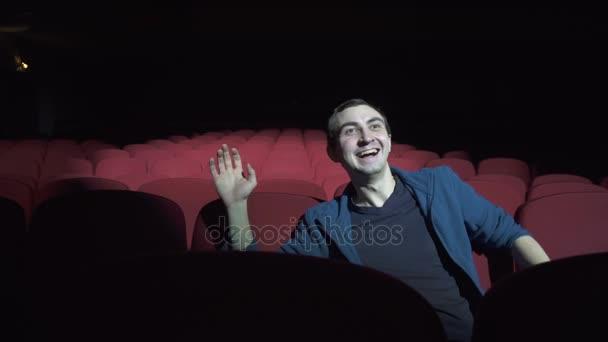 Mann sitzt in bequemen roten Stühlen in einem dunklen Kino, guckt Komödie und lacht