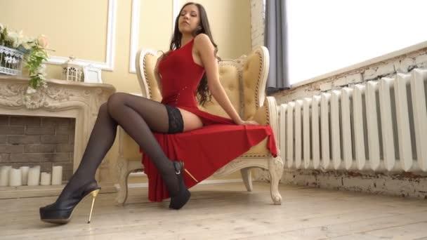 Sexy mladá žena sedí na židli v červených šatech a sexy pózování pro fotografa