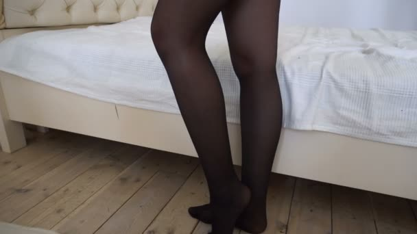 Shapely female legs in black stockings on the background of beds