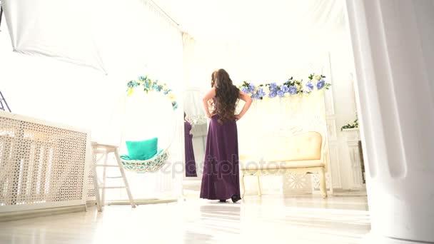 schönes Mädchen sah sich im Bodenspiegel auf luxuriösem weißen Interieur an.