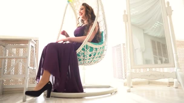 beautiful girl in purple dress sits in round rattan chair on luxury interior