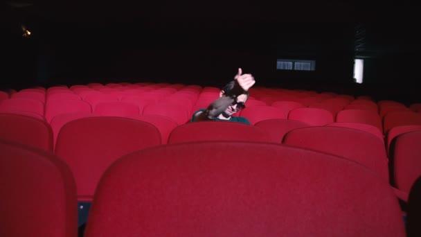 Egy ember ül a kényelmes piros székek, a sötét mozi Színház nevet és tapsol
