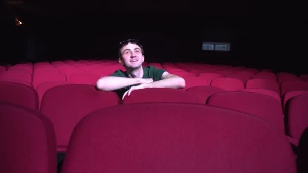 ein Mann, der in bequemen roten Stühlen im dunklen Kinosaal sitzt, sieht lustig aus und lacht