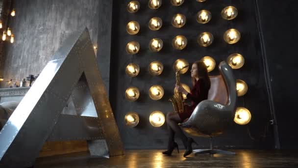Dívka v šatech s saxofon sedí na otočná židle v retro místnosti poblíž velké písmeno A