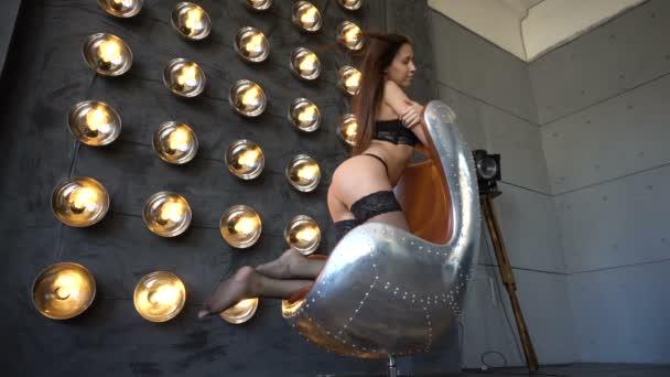 Sexy žena sedící na židli a pózy v ateliéru v černém prádle proti cool retro nástěnné lampy