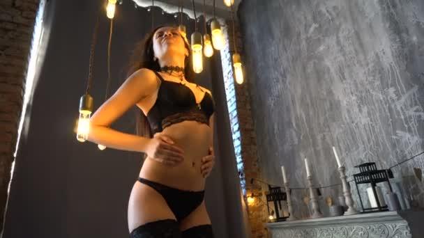 Docela sexy dívka v černém prádle stojící na posteli a představuje ve studiu.