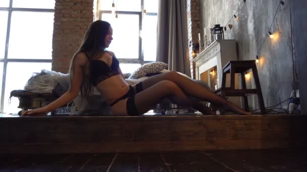 Sexy mladá žena v prádle s krásnými dlouhými vlasy pózuje na dřevěnou podlahu. Studio záběr