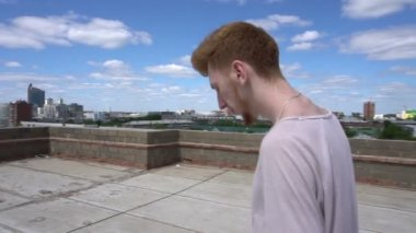 Man walking on roof back and forth along fence on background of sky