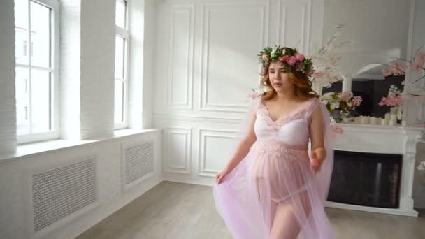 Schwangere schöne Mädchen in lila Frisiermantel und Kopf Blumenkranz ...