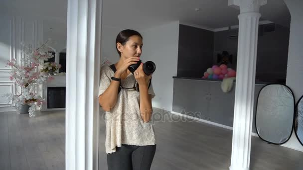 Frau-Fotograf mit Dslr-Kamera im Fotostudio mit Luxus-Interieur