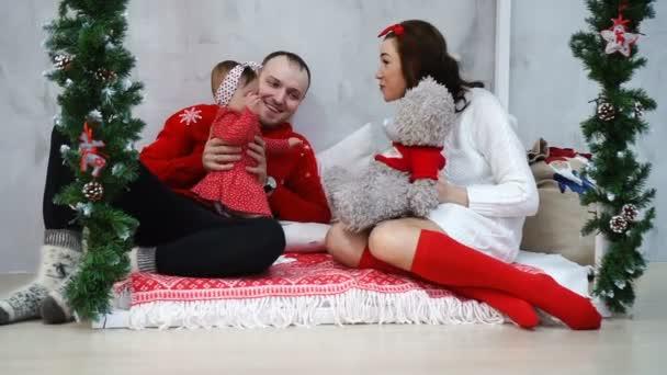 Fiatal kaukázusi szülők játszanak a kis édes baba-lány szép plüssmackó, karácsony ünnep