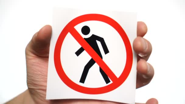 No pedestrian traffic prohibited allowed sign isolated. Male hand holding warning sign
