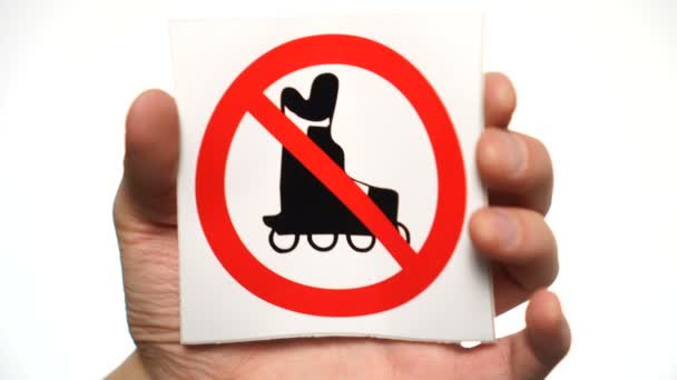 Žádné kolečkové bruslení povoleno znamení izolované. Mužská ruka drží žádné kolečkové brusle znamení