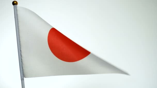 Japanese flag on flagpole flying and waving in the wind.