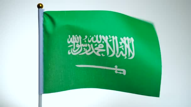 Flag of Saudi Arabia on flagpole flying and waving in the wind.