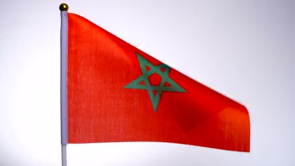 Moroccan flag on flagpole flying and waving in the wind.