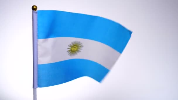 Argentinian flag on flagpole flying and waving in the wind.