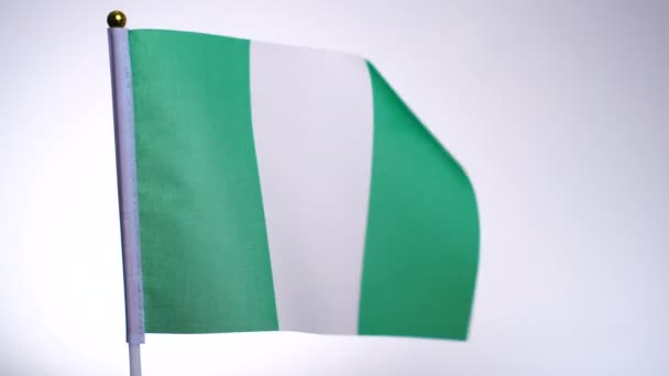 Nigerian flag on flagpole flying and waving in the wind.