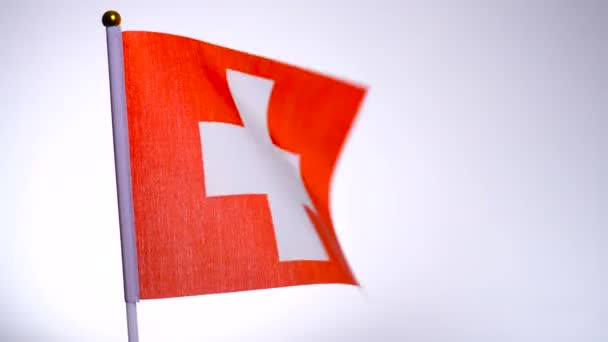 Swiss flag on flagpole flying and waving in the wind.