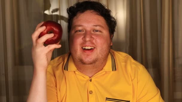 Happy man holding red apple