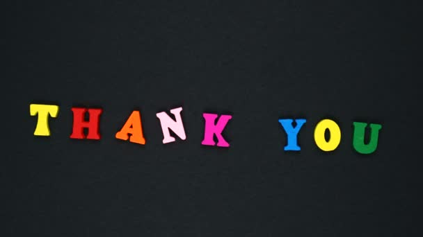 Word thank you formed of wooden multicolored letters. Colorful words loop.